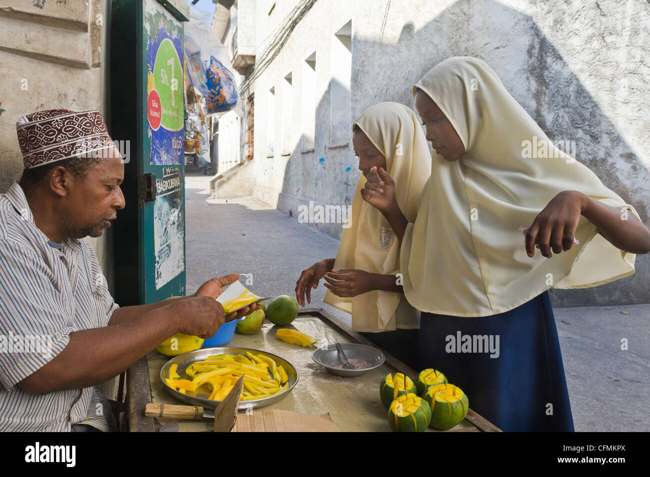 Girls with with headscarf buy fresh mangoes from a vendor in Stone Town Zanzibar Tanzania - Stock Image