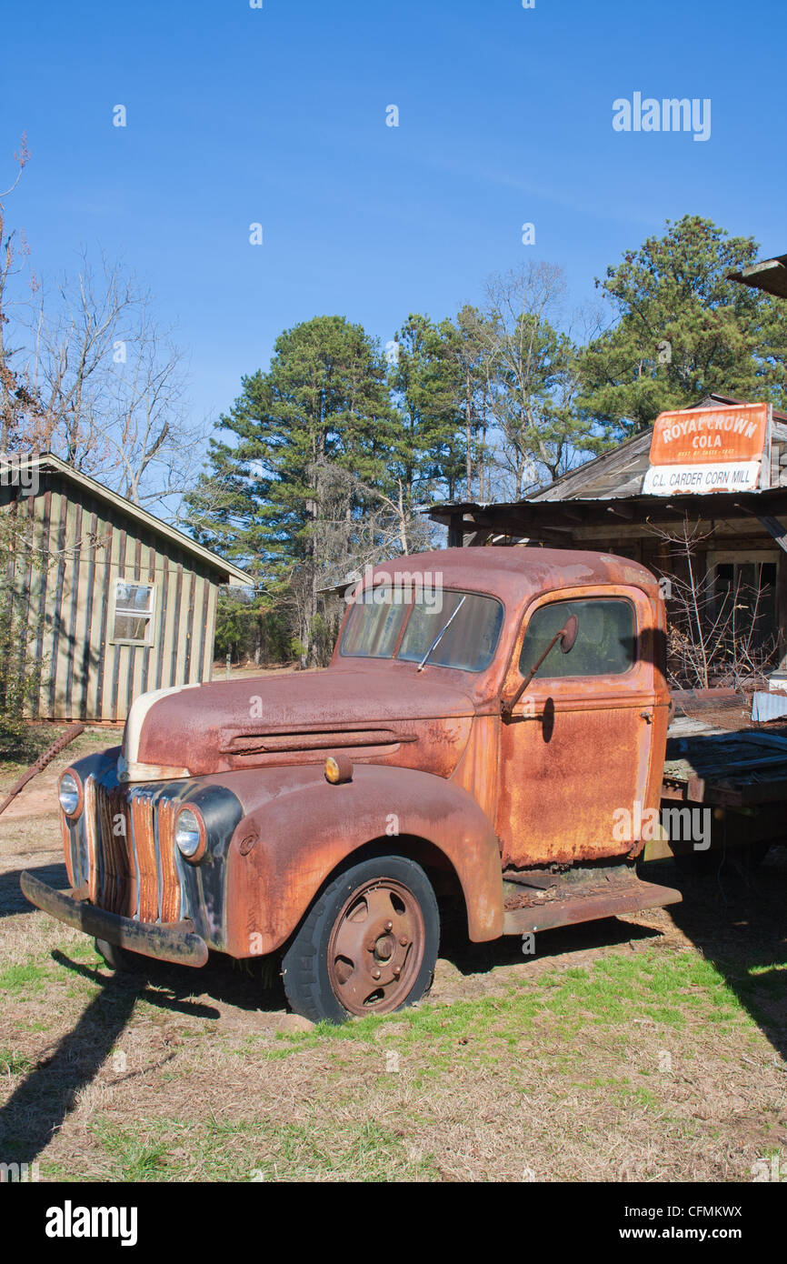 An old rusty antique truck sits beside an old store from the same era. - Stock Image
