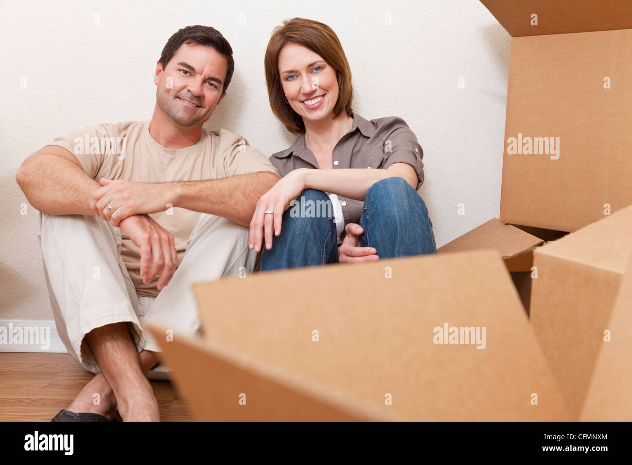 Happy couple in their thirties relaxing while unpacking or packing boxes and moving into a new home. - Stock Image