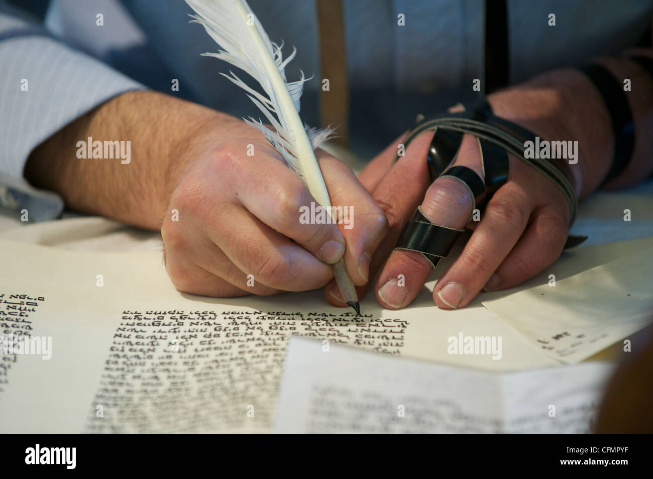 A Jewish scribe known as a Sopher writing Hebrew letters onto parchment forming a new Sefer Torah scroll.  Wearing - Stock Image