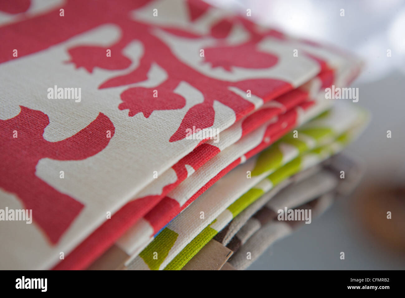 Pile of handmade silkscreen textile dish cloth in bright colors. - Stock Image