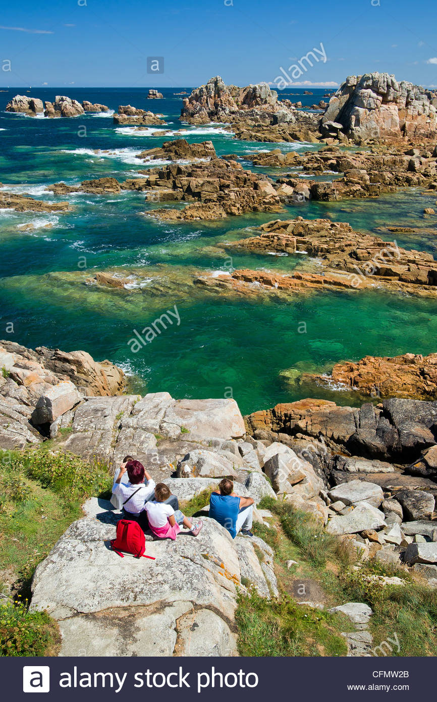 Family enjoying the view of pink granite rocks and clear water at Plougrescant (near Perros Guirec) - Brittany  Stock Photo