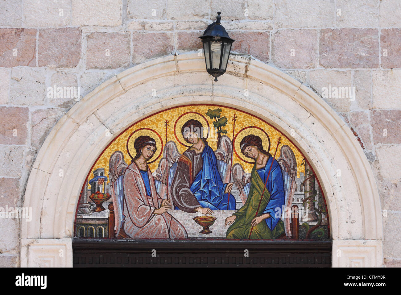 A mosaic icon of the Holy Trinity over the door of the church in old city. Budva, Montenegro - Stock Image