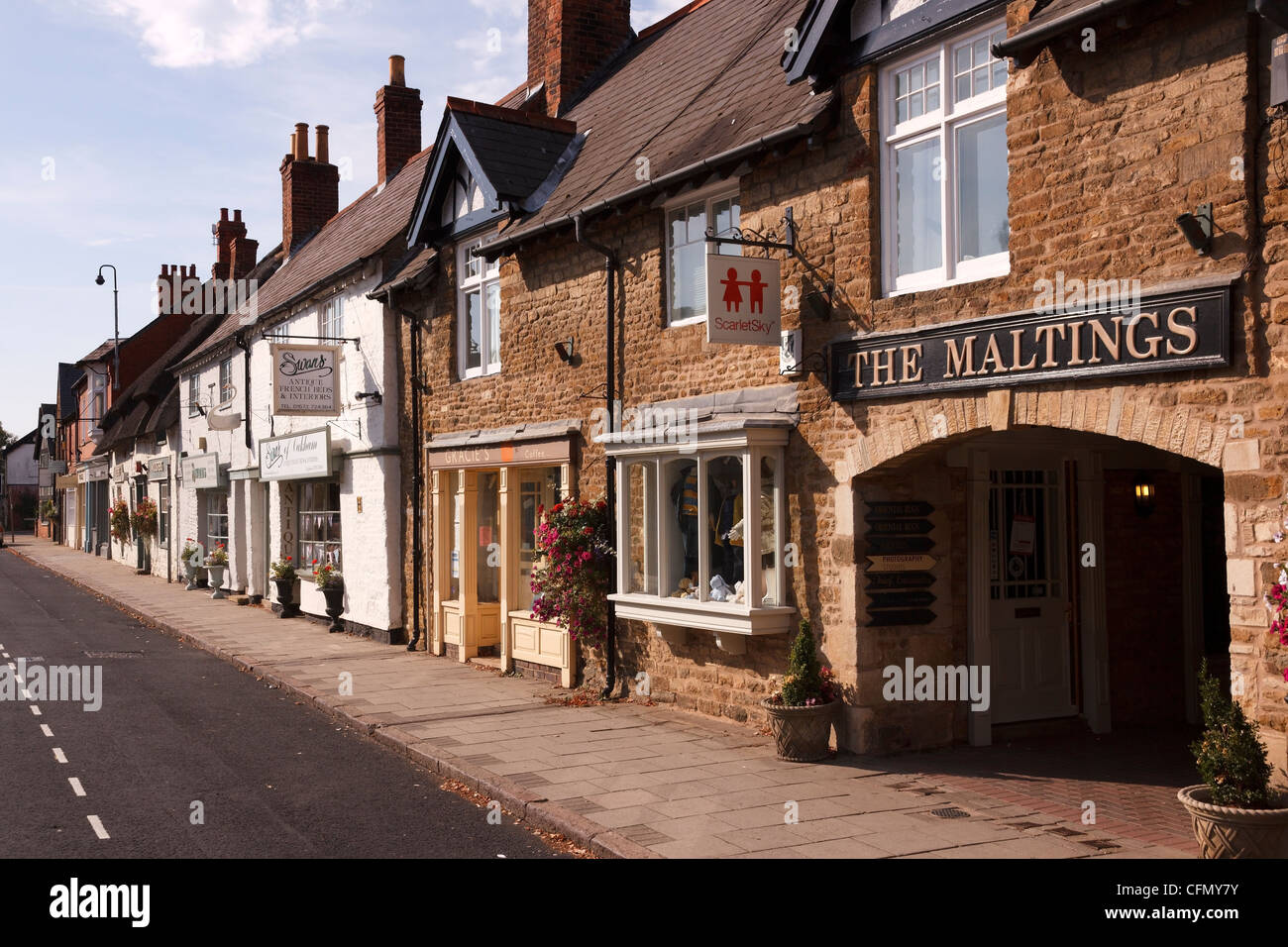 A row of traditional old shop fronts, signs and along town centre shopping street, Mill street, Oakham, Rutland, - Stock Image