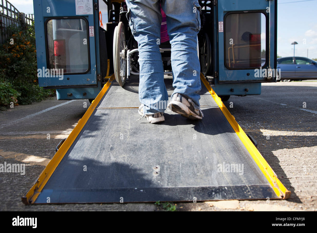 Wheelchair being pushed up ramp on to bus - Stock Image