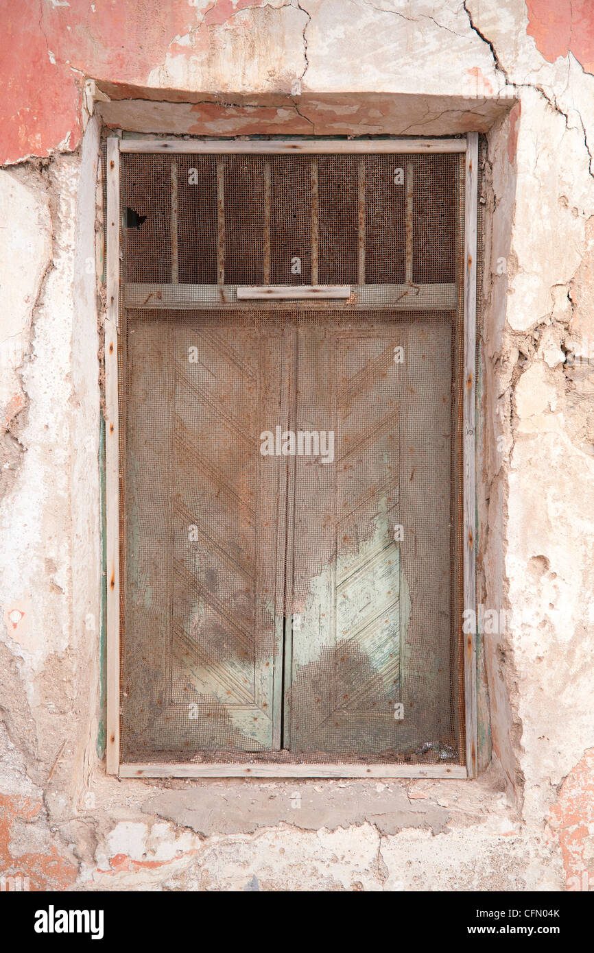Old shuttered window with decrepit metal screen. - Stock Image