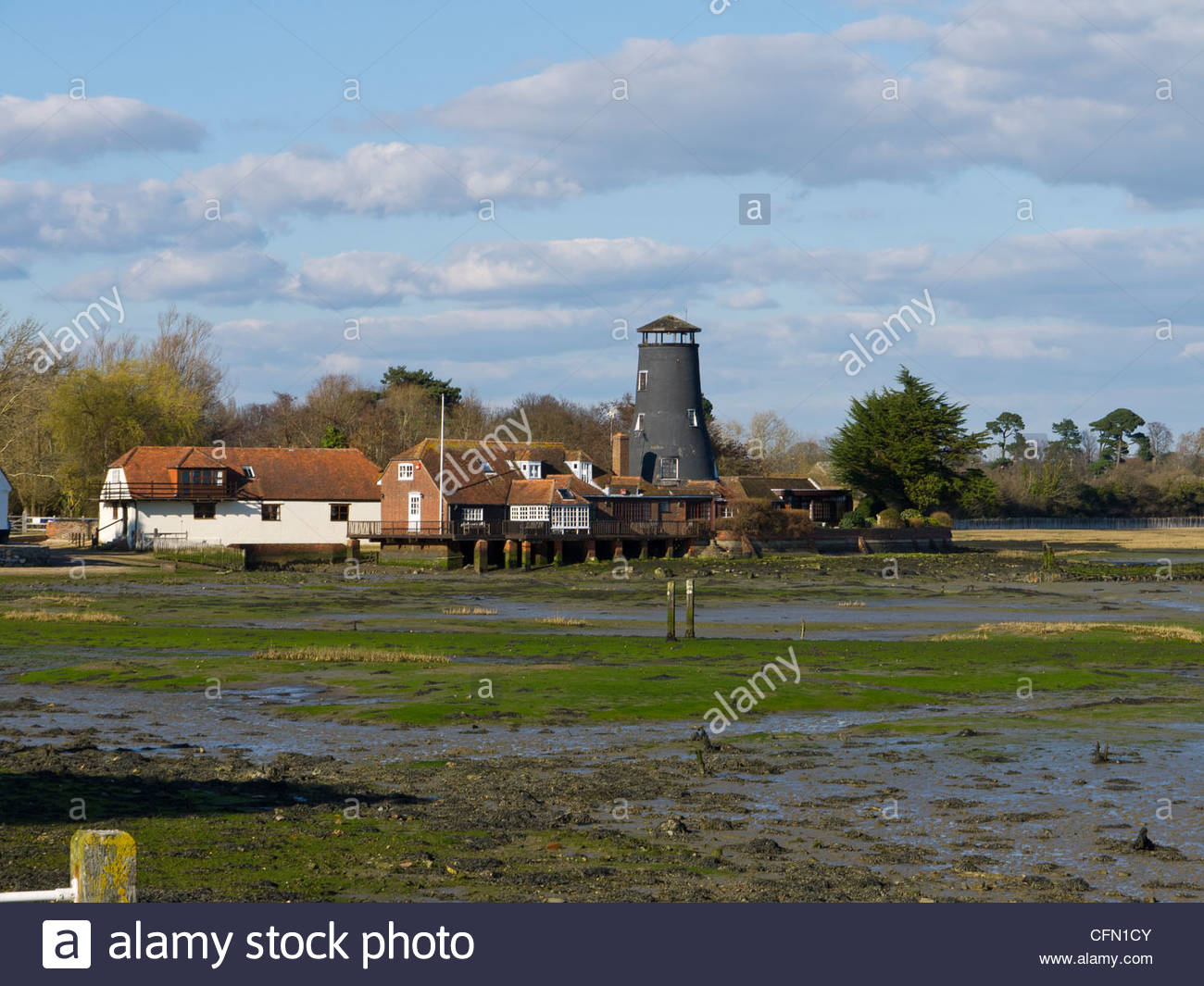 Langstone Mill Royal Oak and house Tide out Hampshire England UK White House Weed Mud Sea - Stock Image