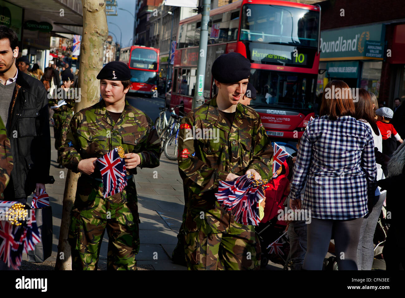 Part time army cadets giving out Union Jack flags to shoppers before a military parade - Stock Image