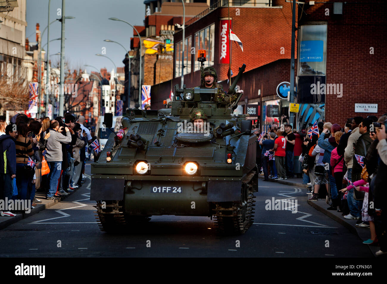 Troops in armoured vehicles drive past High street shops during a Royal Yeomanry parade, spectators watch from the - Stock Image