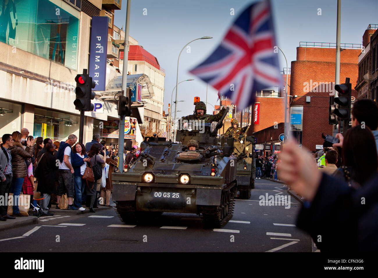 Troops in armoured vehicles drive past High street shops during a Royal Yeomanry parade, spectators wave union jack - Stock Image