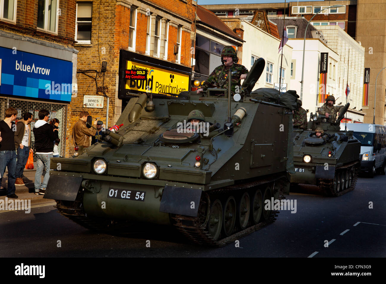 Troops in armoured vehicles drive past High Street shops during a Royal Yeomanry parade - Stock Image