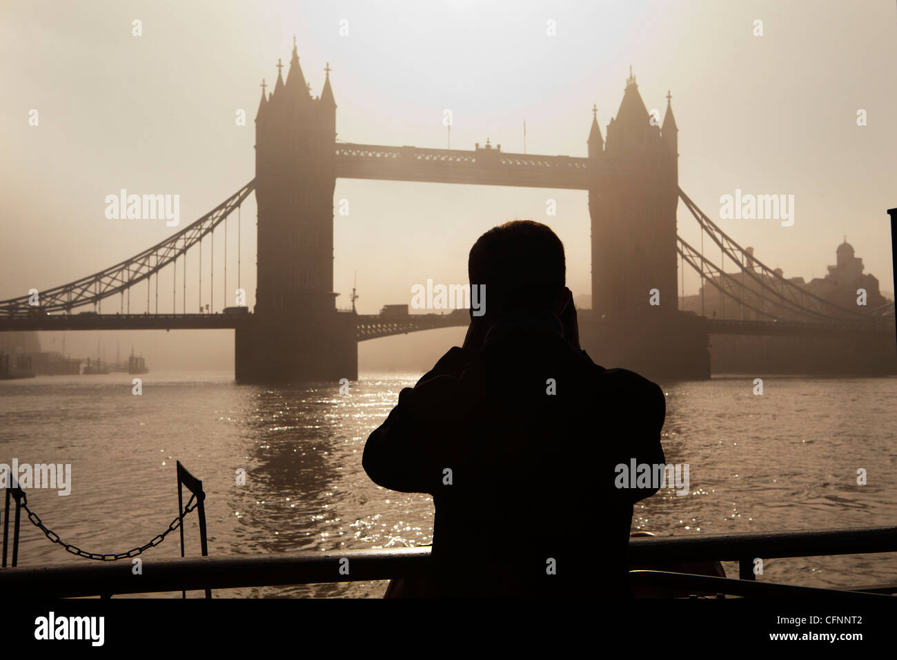 the silhouette of a tourist taking a photograph of Tower Bridge at dawn - Stock Image