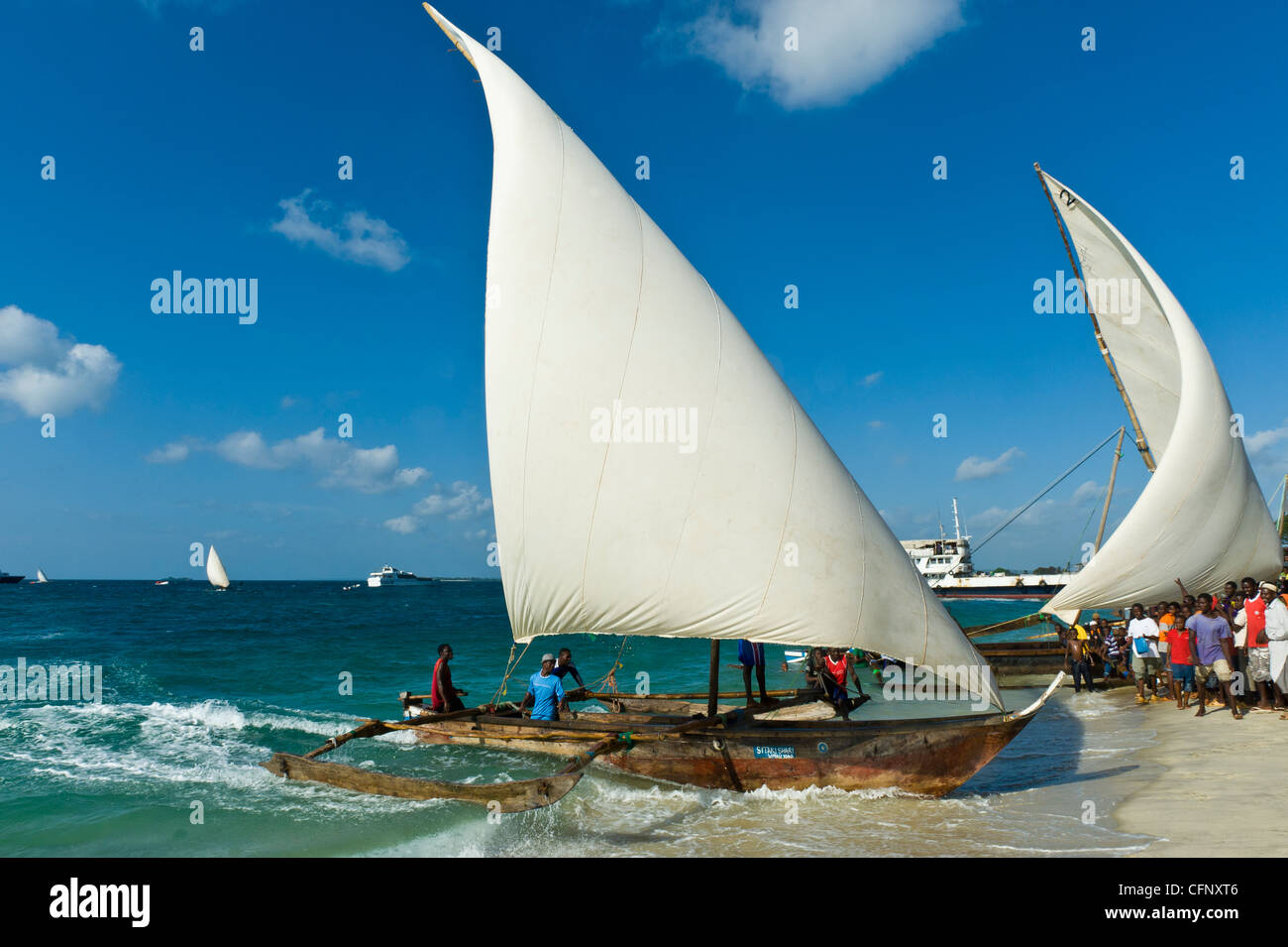 'Ngalawa' traditional out-rigger fishing boats arriving at the finish of a regatta in Stone Town Zanzibar - Stock Image