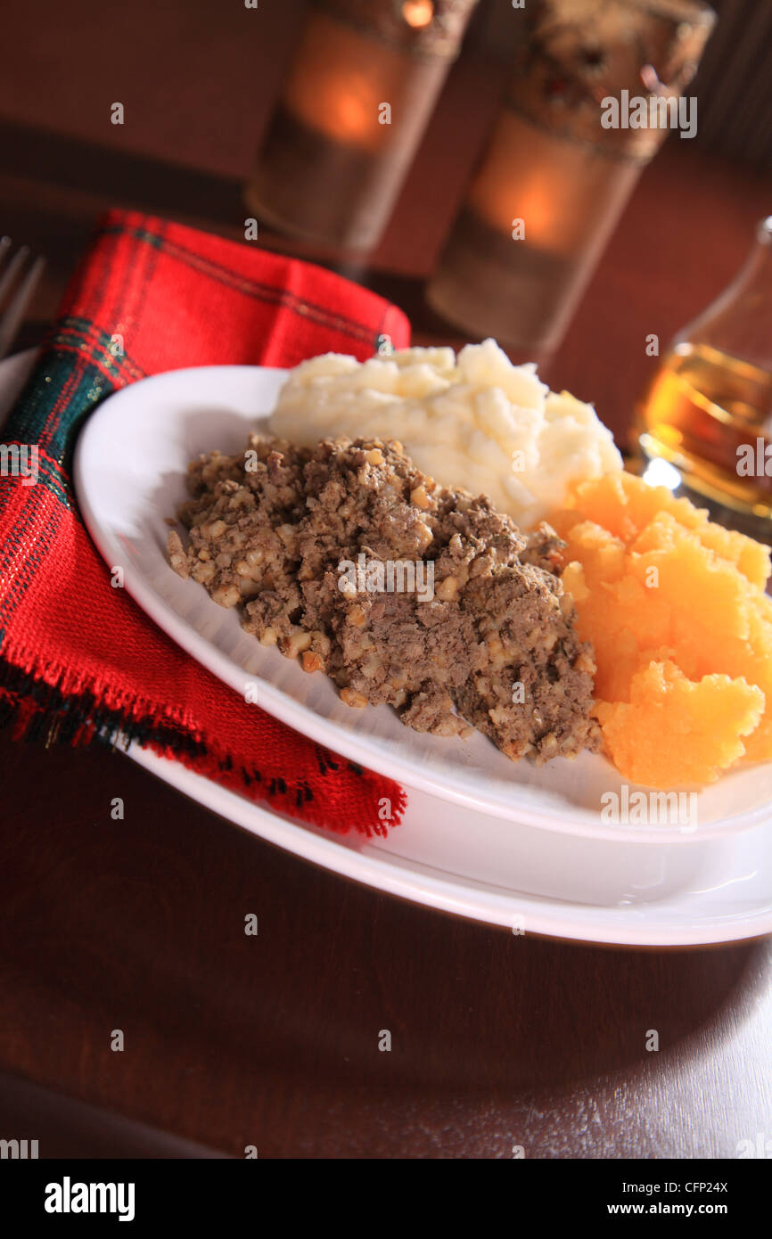 Scottish Haggis Serving For A Burns Night Dinner Against A Royal Stuart Tartan Stock Photo
