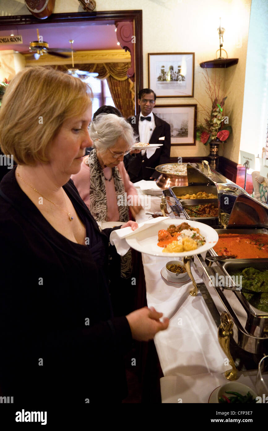 People serving themselves food in the Tamasha Indian restaurant, Bromley, Kent UK - Stock Image