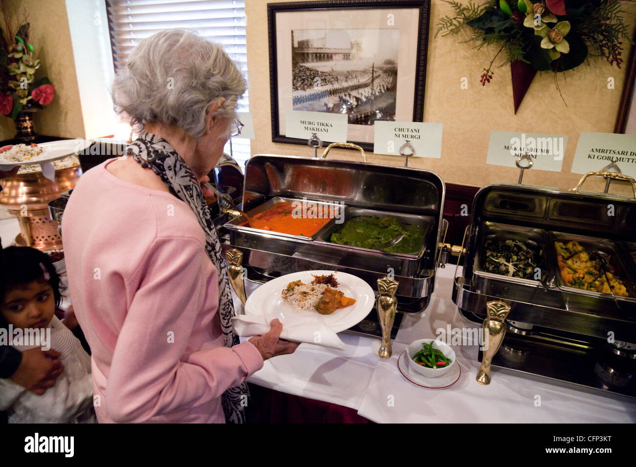 An elderly lady serving herself food in the Tamasha Indian restaurant, Bromley, Kent UK - Stock Image