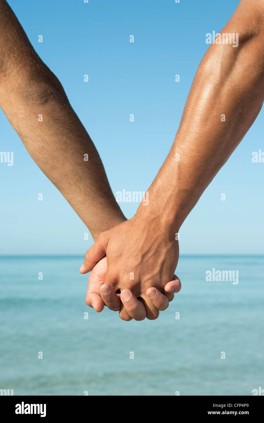 Two men holding hands, cropped - Stock Image