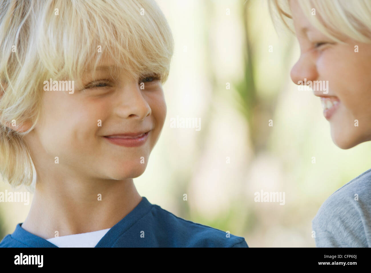 Young brothers smiling at each other - Stock Image