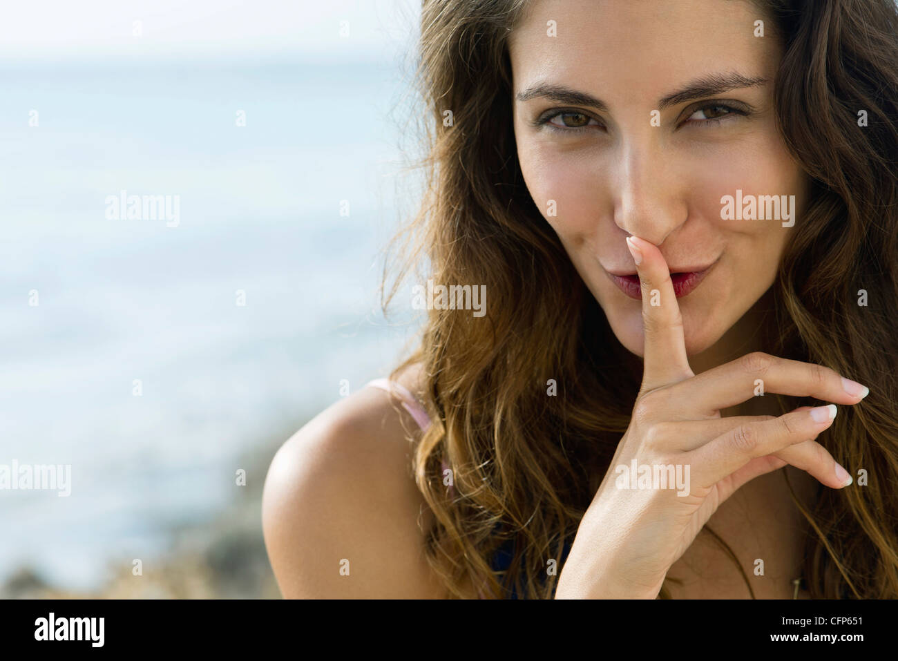 Young woman with finger on lips, portrait - Stock Image