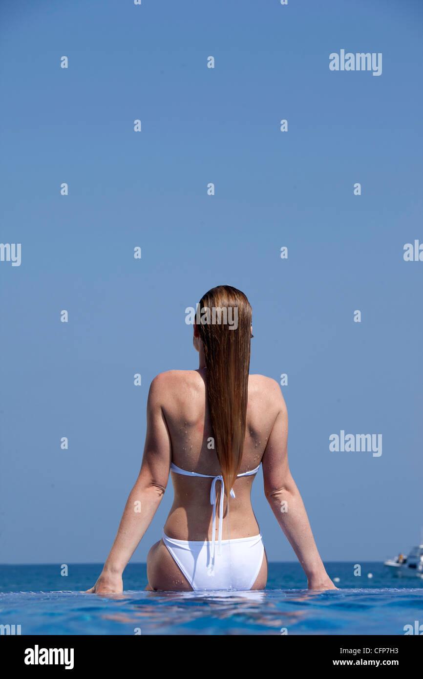 Woman in infinity pool, Kuramathi Island, Ari Atoll, Maldives, Indian Ocean, Asia - Stock Image