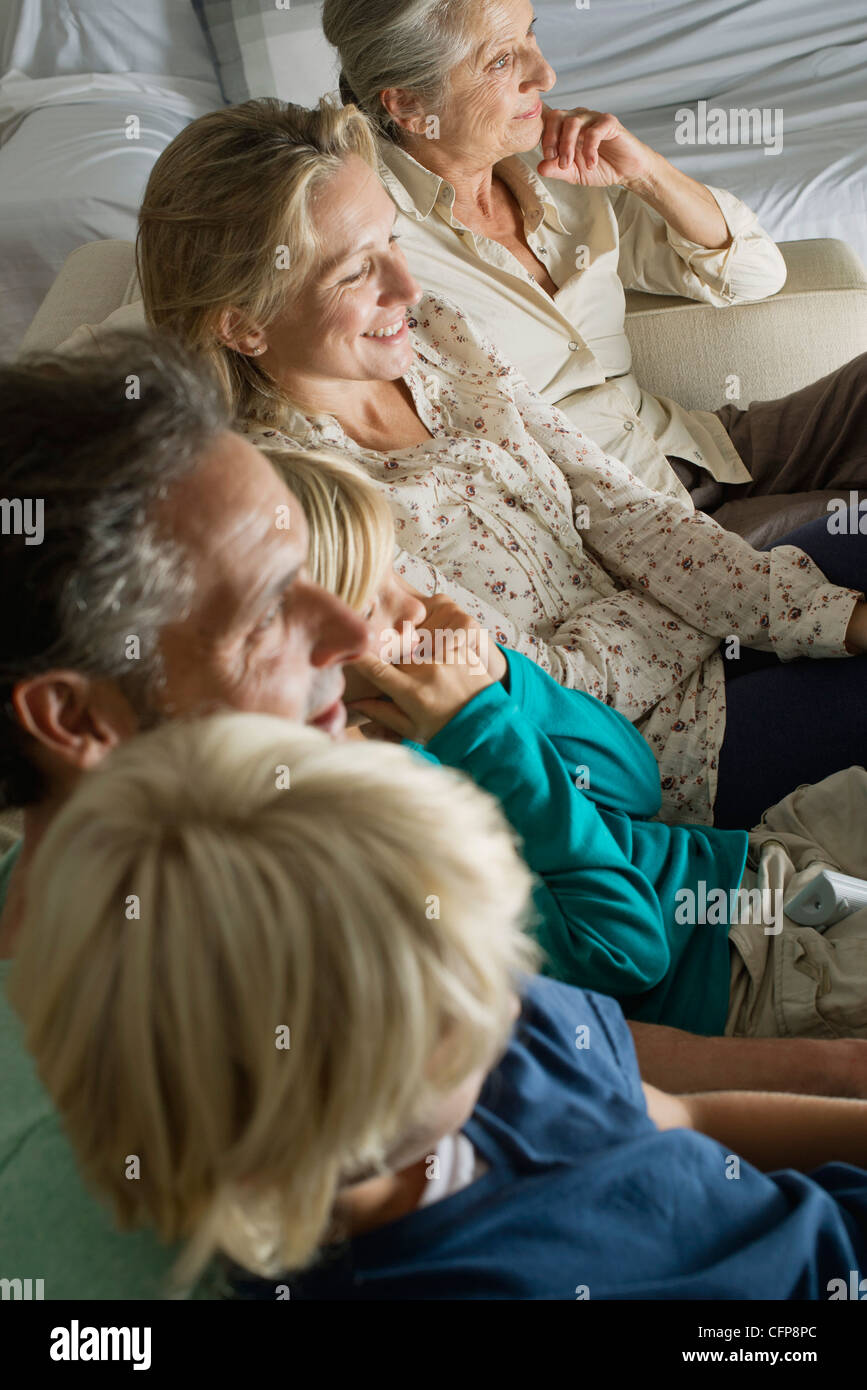 Multi-generation family sitting side by side on sofa, high angle view - Stock Image