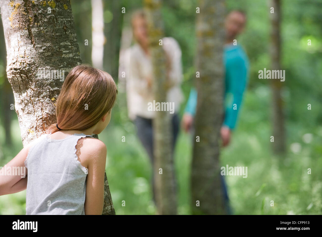 Girl playing hide and seek with parents in woods, rear view - Stock Image
