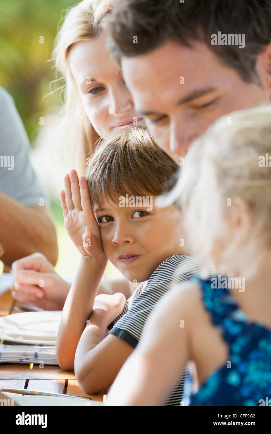Boy having meal with family outdoors - Stock Image