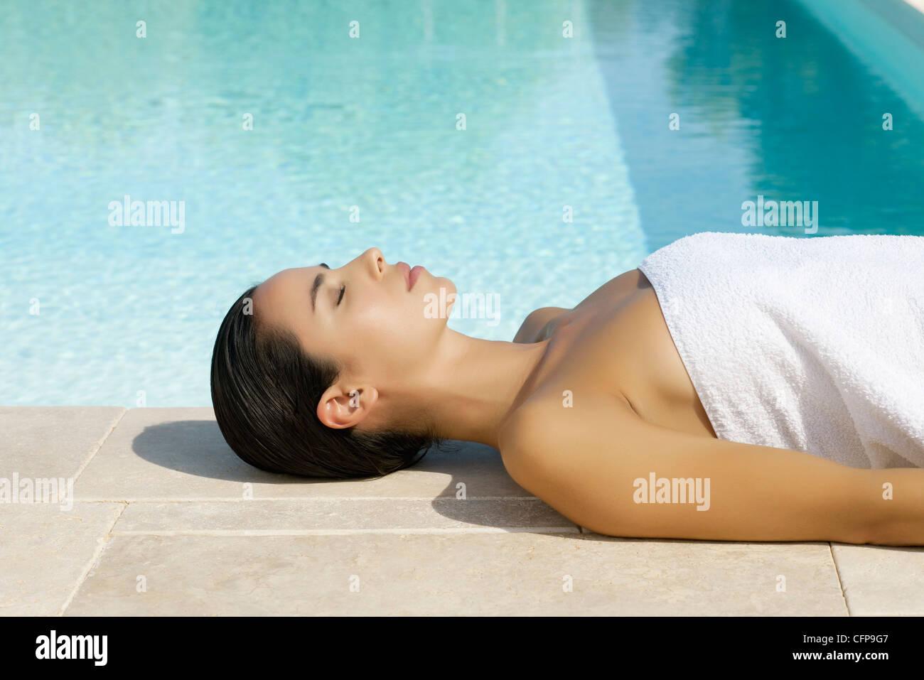 Woman sunbathing by pool - Stock Image