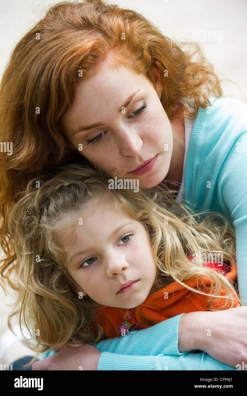 Mother embracing daughter, portrait - Stock Image