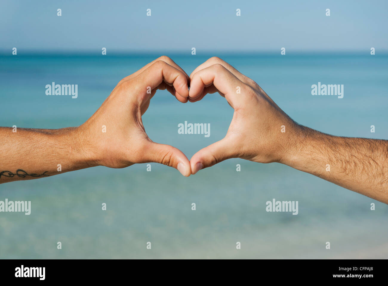 Two men's hands forming heart shape by ocean, cropped Stock Photo