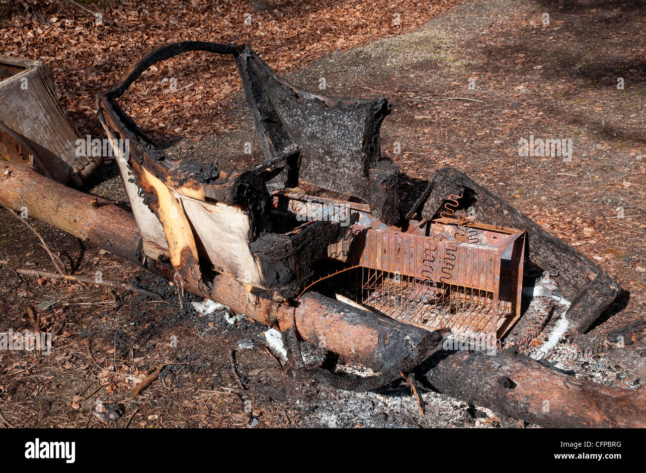 burnt out chair in countryside - Stock Image