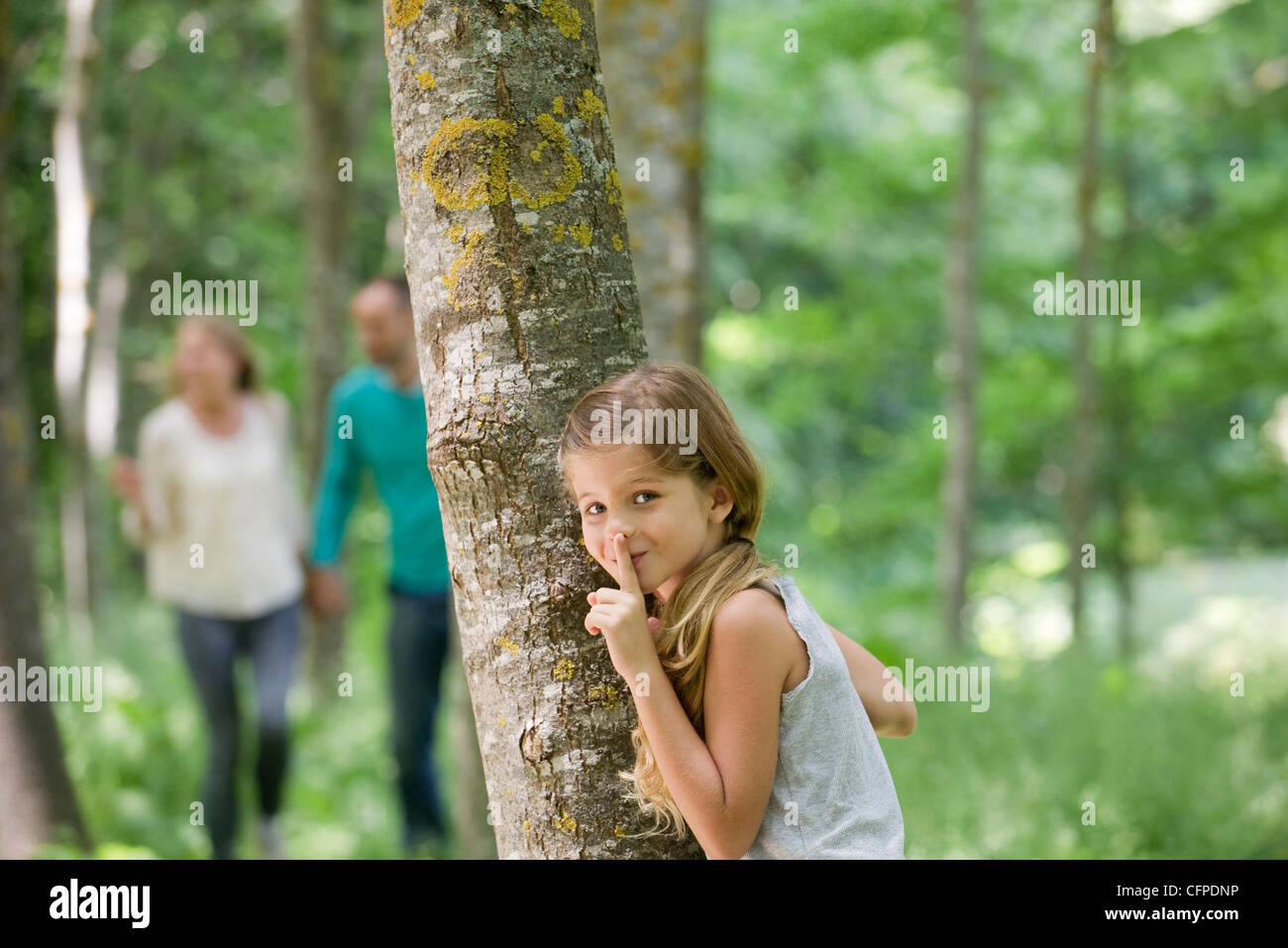 Girl hiding behind tree with finger on lips Stock Photo