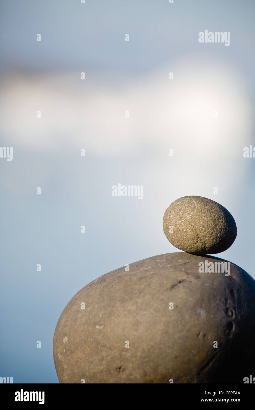 Small stone stacked on top of larger stone - Stock Image