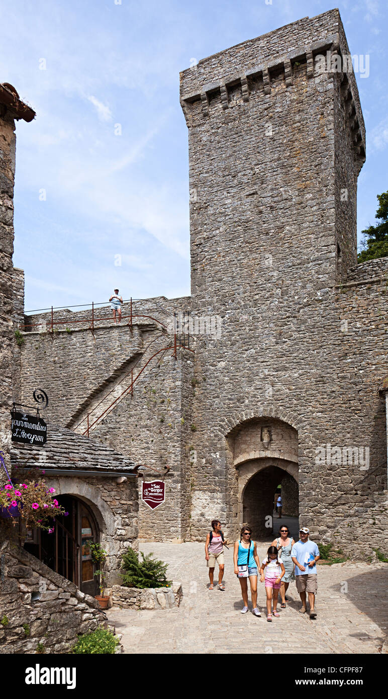 Family walking past entrance gateway to the Knights Templar fortified town the Cite de la Couvertoirade, Aveyron, - Stock Image