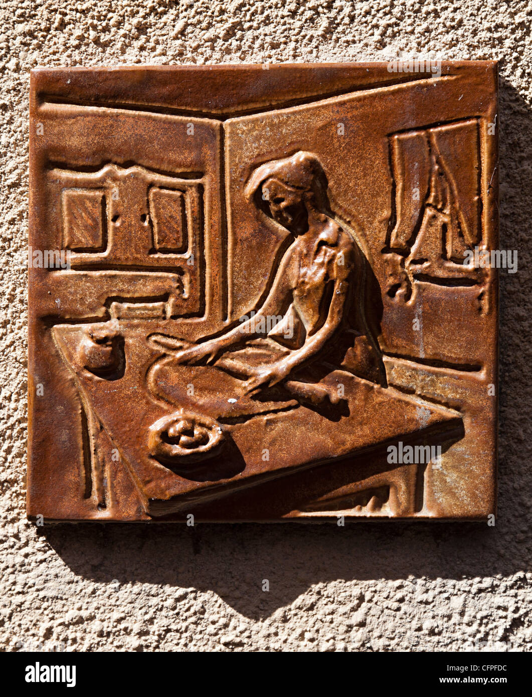 Pottery symbol of woman baking set into wall of patisserie baker, Olargues, Herault, haute Languedoc, France - Stock Image