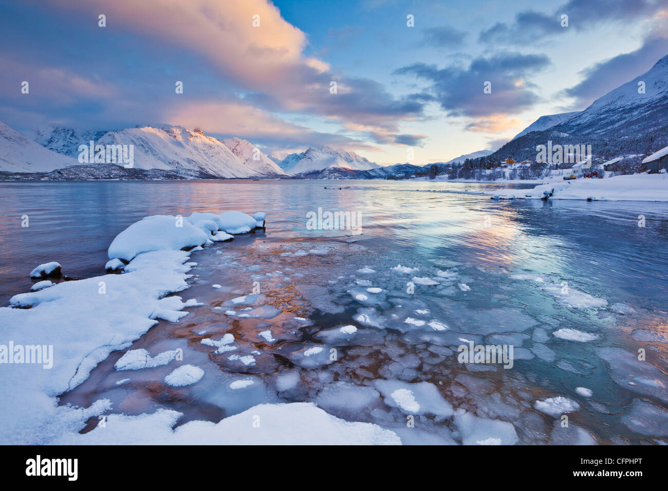 Looking across the frozen sea of Ullsfjord from Sjursnes, towards the Southern Lyngen Alps, at sunset, Troms, Norway, - Stock Image