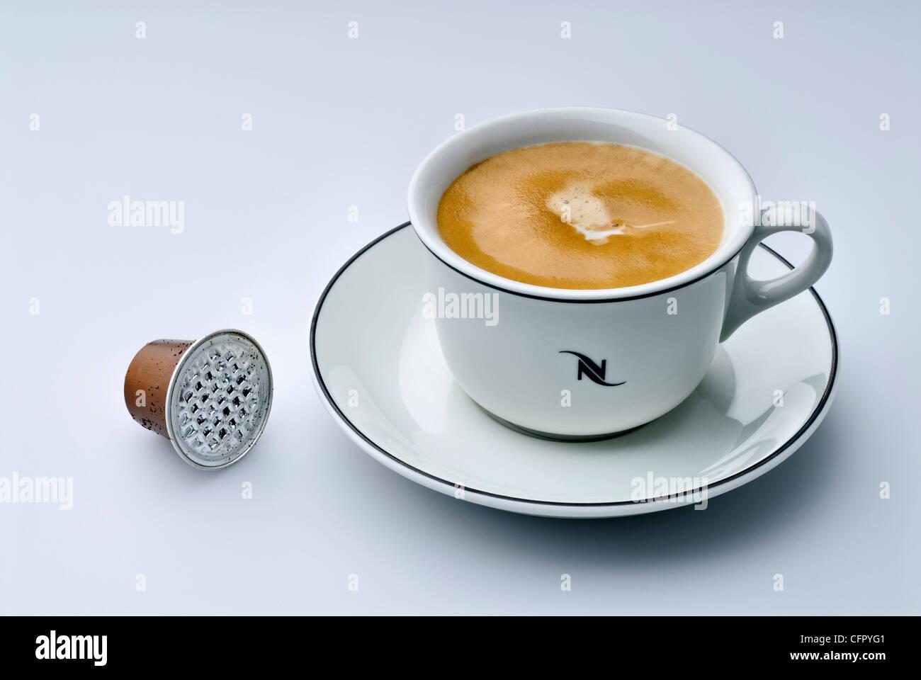 Nespresso cup of fresh made espresso lungo with empty capsule - Stock Image