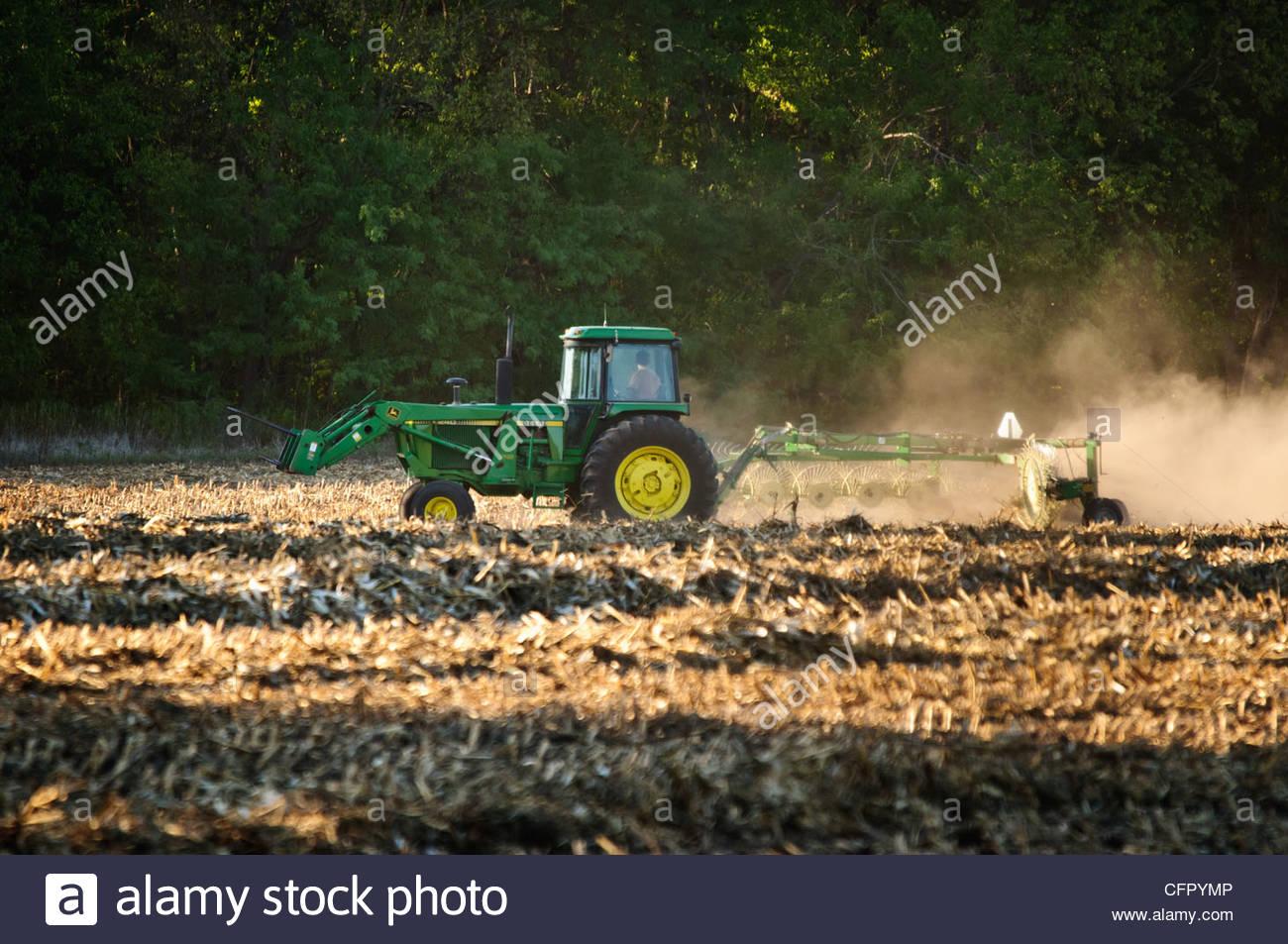 John Deere Tractor using rake wheel on field, Rural Butler County, Sept 22, 2011 - Stock Image