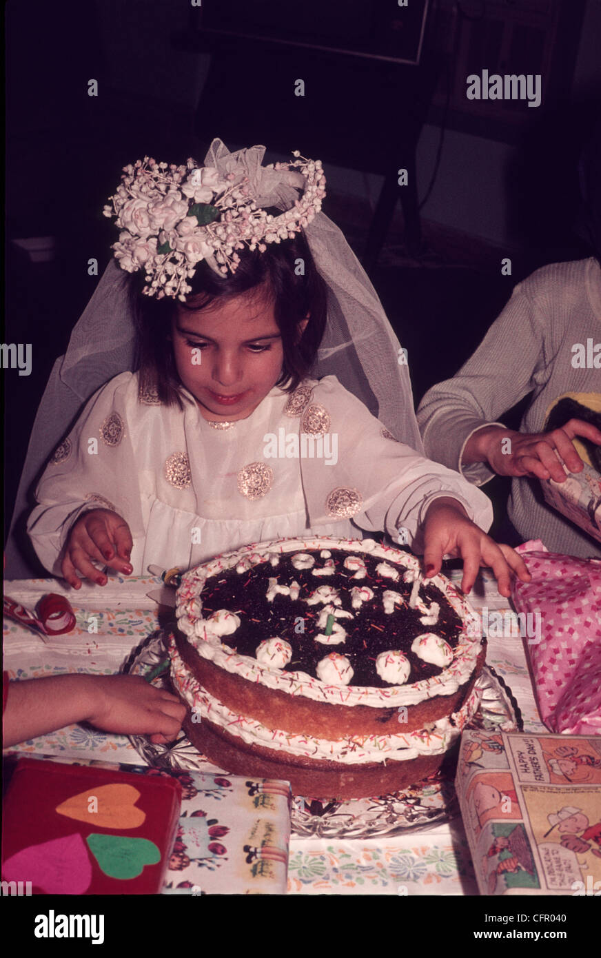 ARAK, IRAN:  Young Iranian girl dressed as a bride, celebrates her fifth birthday by blowing out candles on her - Stock Image