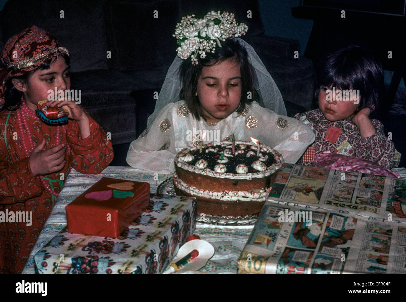 ARAK, IRAN: Young Iranian girl dressed as a bride, celebrates her fifth birthday by blowing out candles on her cake - Stock Image