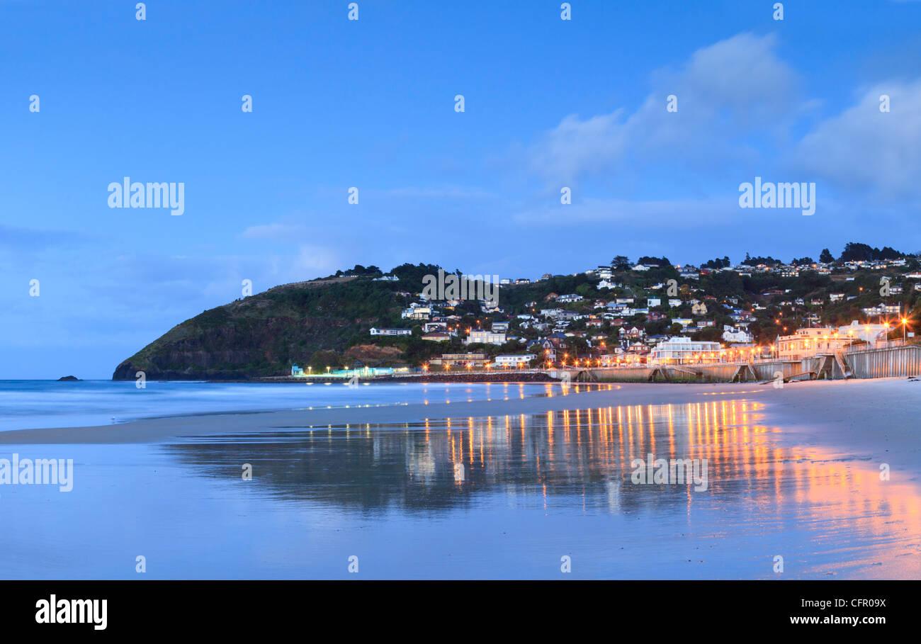 The Dunedin beach suburb of St Clair, Otago, New Zealand, illuminated at twilight. - Stock Image