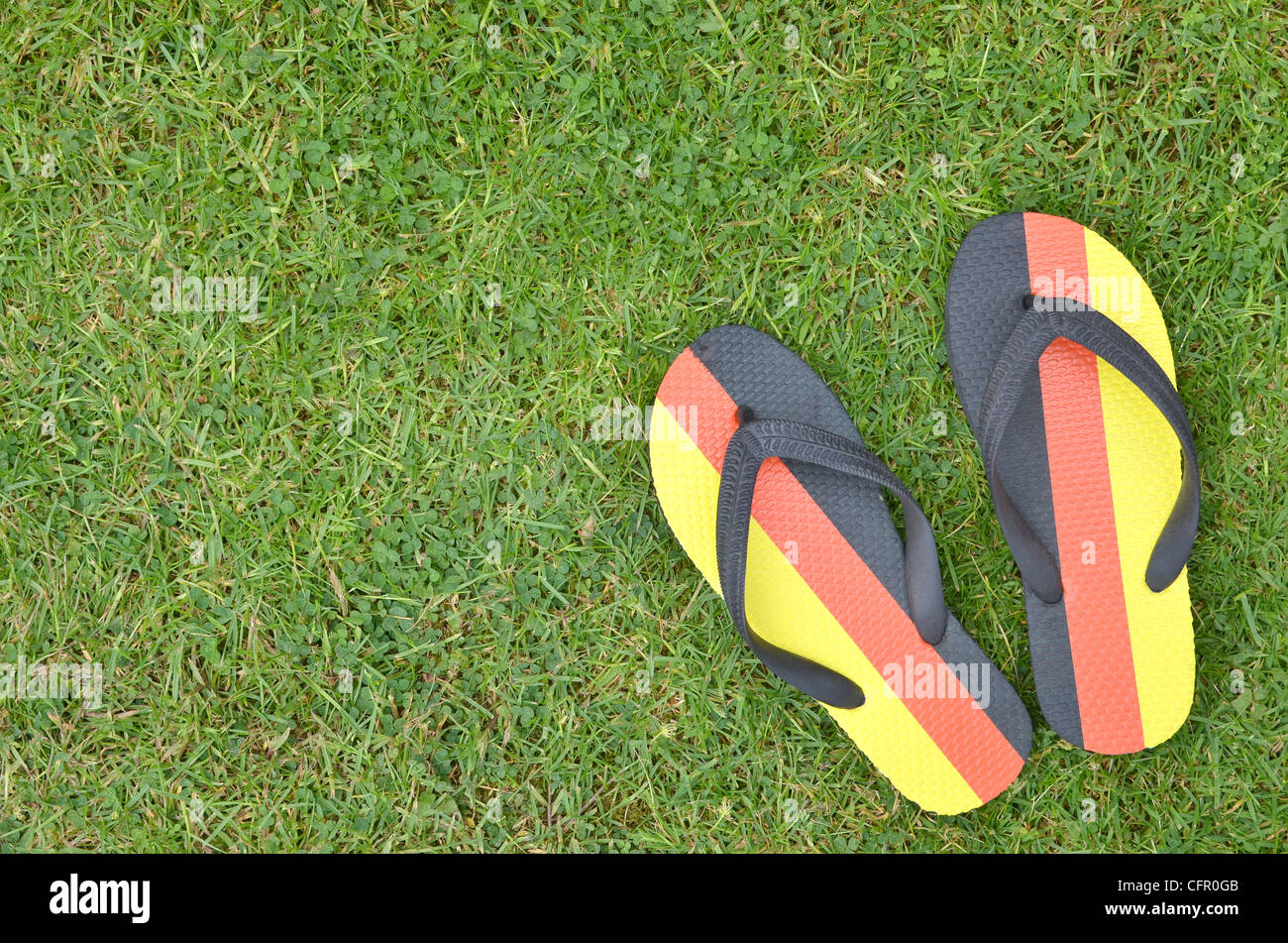 Germany flag printed flip-flops placed on the grass - Stock Image