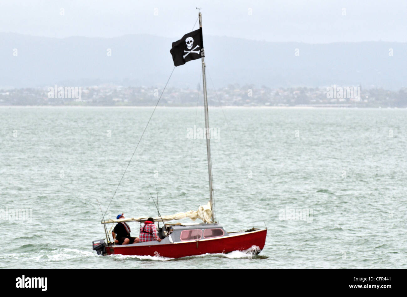 A sail boat with Jolly Roger - Flag of a Pirate skull and crossbones. - Stock Image