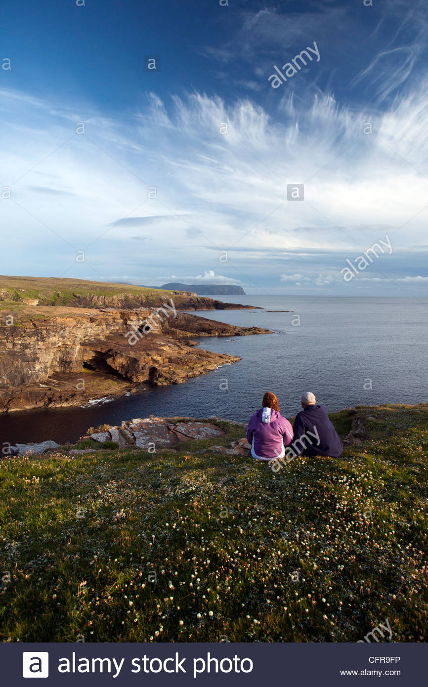 Couple looking at the view,  Yesnaby, Orkney Isles. Cliffs on Island of Hoy in distance. - Stock Image