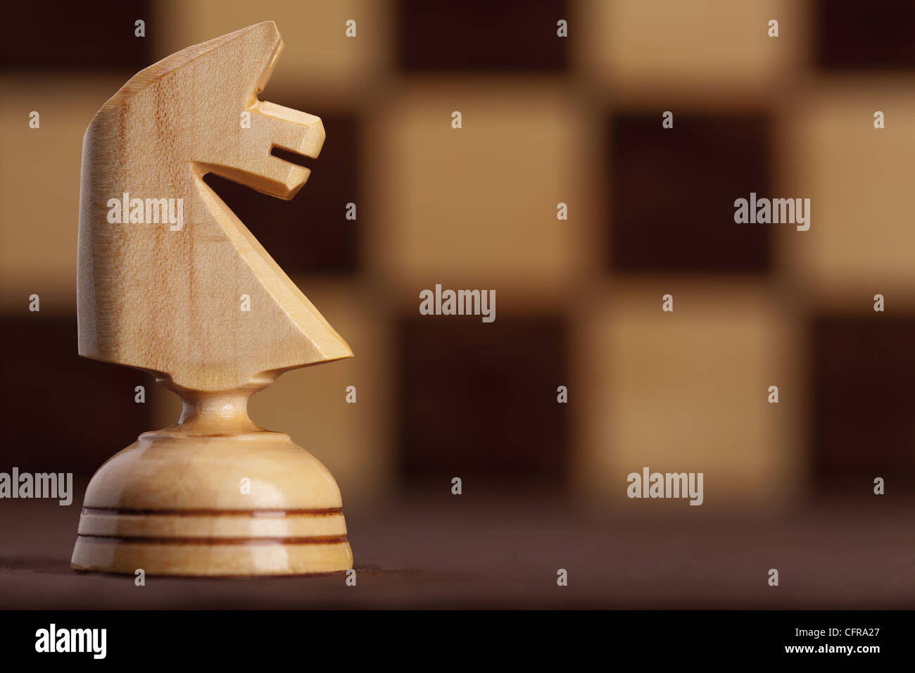 wooden white knight on chessboard background - Stock Image