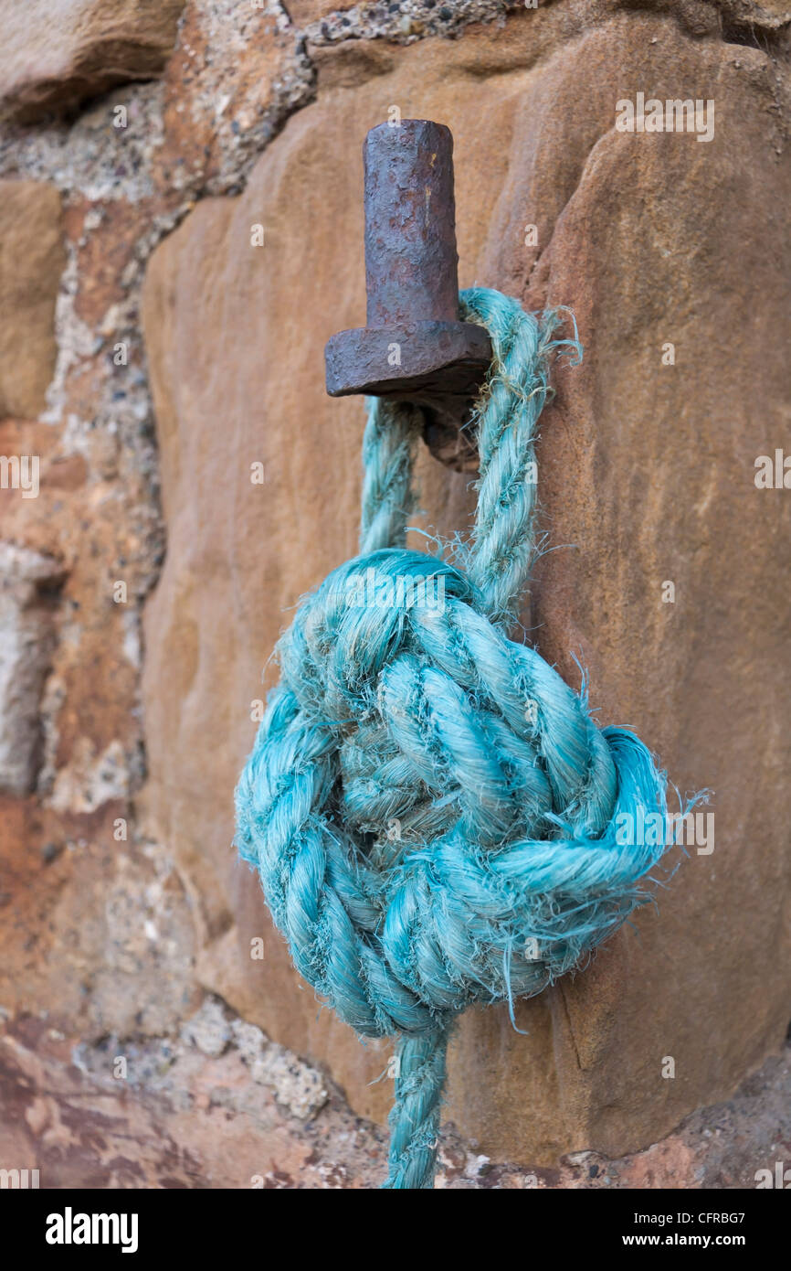 Blue nylon mooring rope tied to an old iron fixture on a harbour wall. - Stock Image