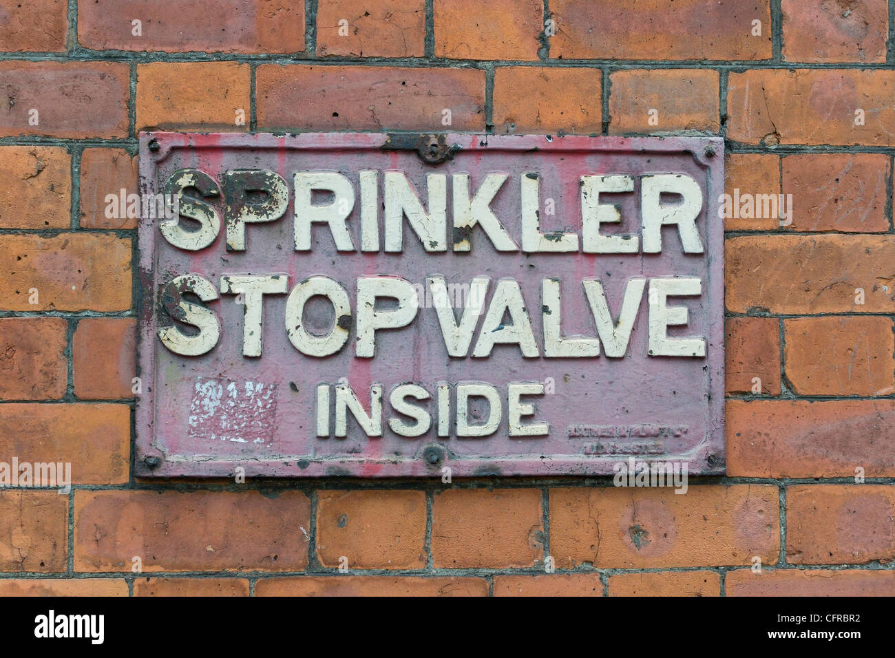 An old 'sprinkler stop valve' sign on the side of a brick building in Manchester. - Stock Image