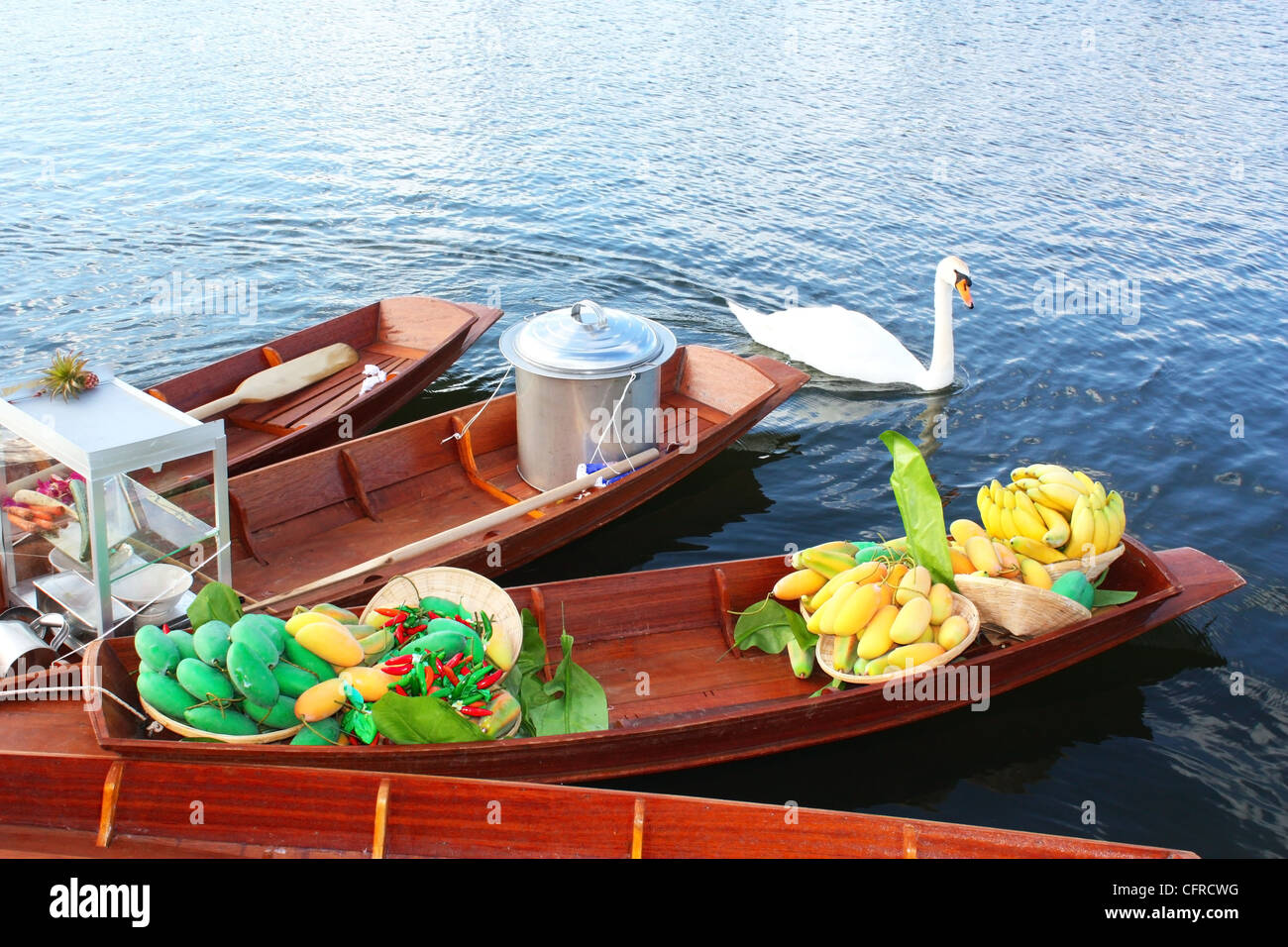 Swan and boats in a lake Stock Photo
