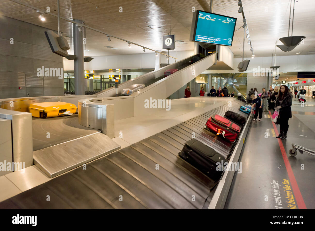 waiting for suitcases at the Luggage carousel in arrivals hall at Oslo Airport Norway Europe - Stock Image
