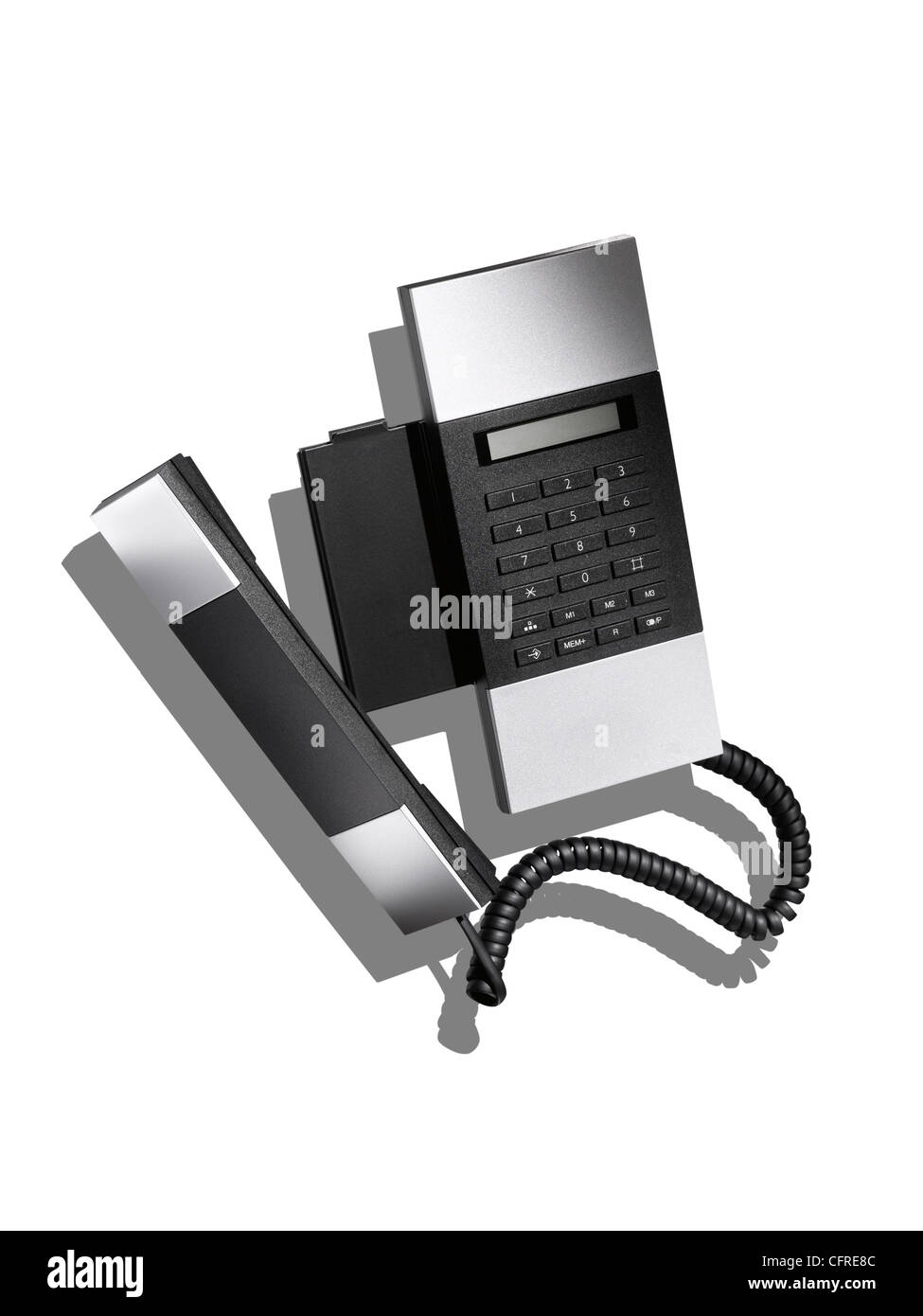 A modern stylish land line telephone on white with creative shadow - Stock Image